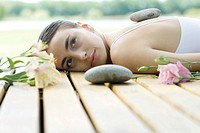 Woman lying on deck with hot stone on back surrounded by flowers and stones