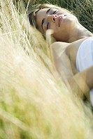 Young woman lying in field with eyes closed, cropped view