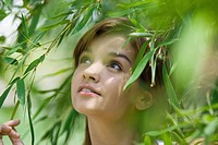 Young woman standing in foliage, looking up, close-up