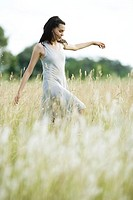 Teen girl walking through field