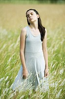 Teen girl standing in field with blade of grass in mouth, portrait
