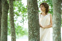 Young woman wearing dress, standing in woods, looking away