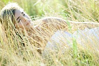 Young woman lying in field, relaxing