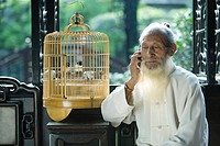Elderly man in traditional Chinese clothing holding cell phone to ear, sitting next to bird cage