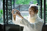 Elderly man in traditional Chinese clothing taking photo with digital camera