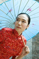 Young woman dressed in traditional Chinese clothing holding parasol over head