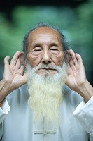 Elderly man in traditional Chinese clothing holding hands behind ears
