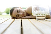 Woman lying on deck, next to container of floating flowers
