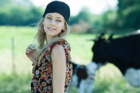 Young woman holding flower in rural setting, smiling at camera, cows in background