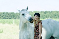Young woman touching horse, smiling at camera