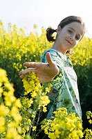 Girl standing in field of canola, arm out to touch flowers