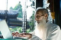 Elderly man wearing traditional Chinese clothing, using laptop