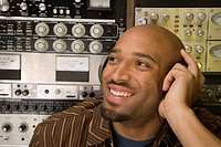 Young man listening to headphones in recording studio (thumbnail)