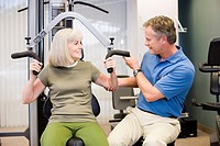 Physical trainer helping woman exercise