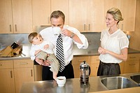 Father holding baby and drinking coffee