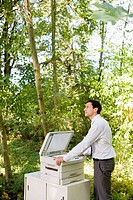 Businessman leaning on copier in woods