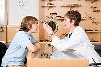 Female optician putting eyeglasses on boy