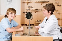 Female optician with boy in office