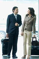 Businessman and a businesswoman looking at each other and smiling at an airport