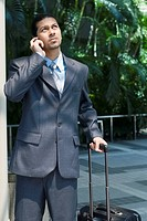 Businessman talking on a mobile phone and holding his luggage