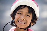 Girl 6-7 wearing bicycle helmet, outdoors, portrait