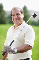 Mature man holding golf club
