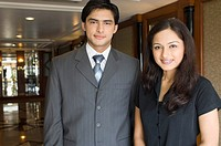 Portrait of a businessman and a businesswoman standing side by side in a hotel