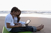 Side profile of a young man sitting on a picnic blanket with a young woman and using a laptop