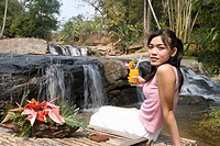Thailand, Chiang Mai, Sukantara Resort, young woman drinking cocktail, sitting in front of waterfall, rear view