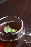 Close-up of a cup of herbal tea with mint leaf in a cup
