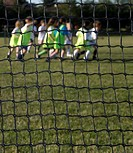 Children 6-7, 8-9 running on football pitch, goal net in foreground