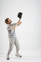 Man wearing baseball glove catching ball, studio shot
