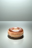 Chocolate glazed doughnut on grey surface, studio shot