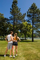 Young couple in sportswear embracing in park, rear view
