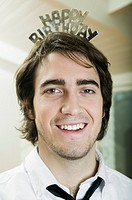 Young man wearing happy birthday crown, indoors, portrait