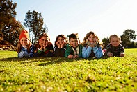 Group of children 5-7 lying on grass in park, portrait surface level