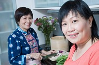 Portrait of a mature woman smiling with her mother cutting vegetables in a kitchen