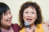 Portrait of a senior woman singing with a mature woman in front of a microphone