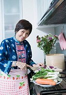 Portrait of a senior woman cutting vegetables and smiling in a kitchen