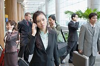 Businesswoman talking on a mobile phone and leaving an airport