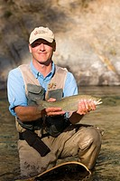 Fly-fishing guide, releases cutthroat trout on tributary of Elk River near Fernie, British Columbia, Canada