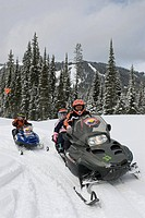 A grandmother and her two grandchildren snowmobile with Sun Peaks Ski Resort in the background, just North of Kamloops, British Columbia, Canada