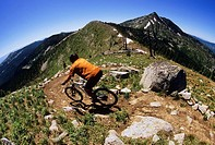 A young man decending on some sweet single track on the Seven Summits trail in Rossland, British Columbia, Canada