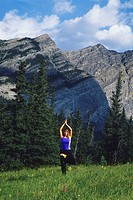 a young athletic woman doing yoga among the trees and mountains in Kananaskis country, Alberta, Canada