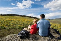 A couple takes a break from hiking to enjoy the wildflowers and view, just South of Kamloops, British Columbia, Canada