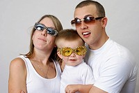 Smiling young family wears sunglasses for eye protection and fun.