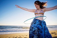 20 year old woman does the hula hoop on the Pacific ocean beach in Los Angeles, California, USA