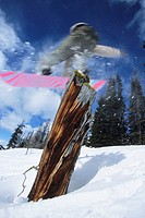 Young male snowboarder flying through the air and jibbing tree stump at Lake louise, Banff National Park, Alberta, Canada