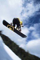 Young male snowboarder catching air at Mt Norquay, Banff National Park, Alberta, Canada