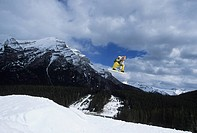 Young male snowboarder jumping in the terrain park at Mt Norquay, Banff National Park, Alberta, Canada